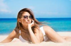 白色泳装的一名年轻深色的妇女在海滩 库存照片