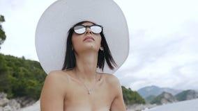 白色泳装的享用太阳和水的少妇有大帽子的和太阳镜坐岩石靠岸 夏天 股票录像
