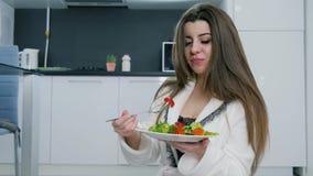 白色浴巾的深色的女孩有沙拉板材的和一把叉子在手上在背景厨房关闭  股票视频