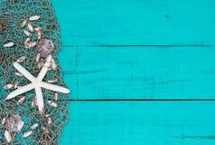 白色海星和壳在鱼网在小野鸭蓝色木海滩签字 库存照片