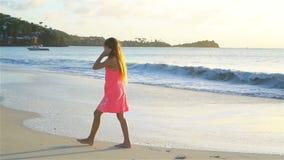 白色海滩的可爱的活跃小女孩在日落 慢的行动 股票录像