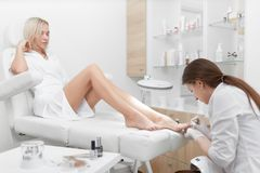 白色清洁表皮的专家在脚和擦亮剂的钉子附近 免版税库存图片