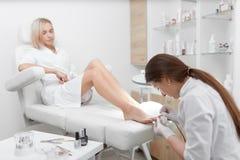 白色清洁表皮的专家在脚和擦亮剂的钉子附近 库存照片