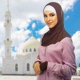白色清真寺背景的回教女孩 免版税图库摄影