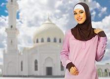 白色清真寺背景的回教女孩 图库摄影