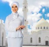 白色清真寺背景的回教女孩 免版税库存图片