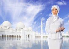 白色清真寺背景的回教妇女 免版税库存图片