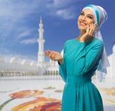 白色清真寺背景的回教妇女 库存图片