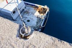 白色渔船栓与钢圆环的绳索在码头, 免版税图库摄影