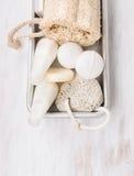 白色温泉卫生间设置了与盐球和化妆水在金属箱子 库存照片