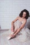白色游泳衣的芭蕾舞女演员为酸疼的腿保持 免版税库存照片