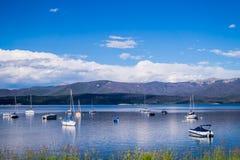 白色游艇、蓝天和蓝色清楚的水盛大湖 钓鱼在落矶山脉 图库摄影