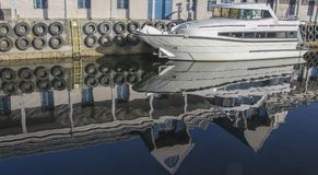 白色游艇和停泊处大厦的反射在水中 库存照片