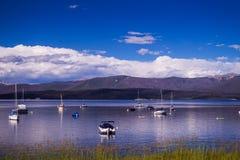 白色游艇和蓝色清楚的水盛大湖 钓鱼在落矶山脉 图库摄影