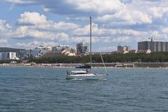 白色游艇在背景住宅群水地区的在Gelendzhik,克拉斯诺达尔地区,俄罗斯黑海 免版税图库摄影