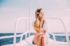 白色游艇的妇女松弛鼻子在海 夏天职业 免版税库存照片
