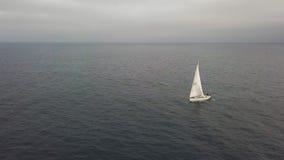 白色游艇航行在海,当在多云天空寄生虫视图时的金黄日落 股票视频