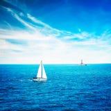 白色游艇航行在镇静蓝色海 灯塔 免版税库存图片