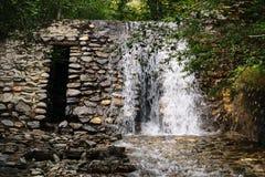 白色瀑布和假山庭园砌石墙壁 免版税库存照片