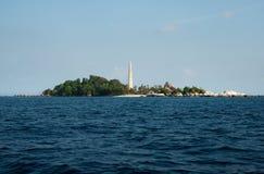 白色灯塔站立在有自然岩层的一个海岛上的和绿色植被在勿里洞岛 免版税库存照片