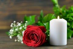 白色灼烧的蜡烛和红色玫瑰 免版税图库摄影
