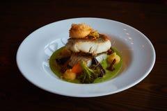 白色炖了在绿色pesto调味汁的鲈鱼与通入蒸汽的硬花甘蓝的菜,红萝卜,甜菜,蘑菇,土豆泥 免版税库存照片