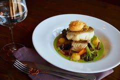 白色炖了在绿色pesto调味汁的鲈鱼与通入蒸汽的硬花甘蓝的菜,红萝卜,甜菜,蘑菇,土豆泥 免版税库存图片