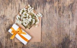 白色烘干了在纸信封和一个箱子的花有与一条金黄丝带的一件礼物的 复制空间 免版税图库摄影