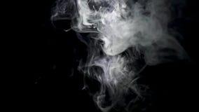 白色烟喷气机在黑背景的 r 白色烟云彩在黑背景上升并且蒸发 股票录像
