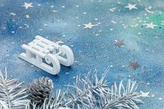 白色爬犁和银圣诞树分支与在蓝色的锥体 库存照片