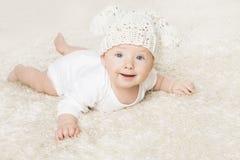 白色爬行在白色毯子的被编织的帽子的愉快的婴孩 免版税库存图片