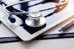 白色片剂和听诊器在桌上 在桌上的医疗设备 库存图片