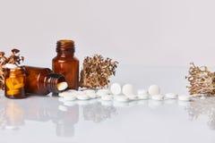 白色片剂和药片与地衣洋岛衣属islandica在白色镜子背景 库存图片