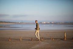 白色牛仔裤和一件衬衣的一个年轻人在湖的一个沙滩 免版税库存图片