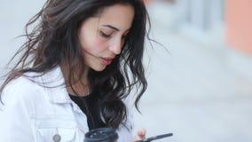白色牛仔裤的年轻的典雅的白种人棕色毛发的女孩用卡片寻找地址的咖啡玻璃涂使用 股票录像