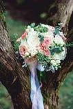 白色牡丹和玫瑰豪华新娘花束在树 免版税库存照片