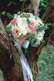 白色牡丹和玫瑰豪华新娘花束在树 库存照片