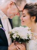 白色牡丹的婚礼花束的特写镜头视图在愉快的新婚佳偶的手上 库存图片