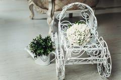 白色牡丹豪华新娘花束在一个白色装饰推车的 库存图片