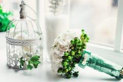 白色牡丹豪华新娘花束在窗台的在窗口前面 免版税库存图片