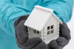 白色玩具房子在戴着黑暗的手套的一个人的手上在冬天 免版税库存照片