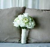 白色玫瑰和莲花在床上的婚礼花束 免版税图库摄影