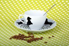 白色瓷咖啡杯特写镜头有匙子的在绿色加点了织品 免版税库存照片