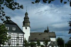 白色用木材建造的房子和教会在温特尔贝尔格德国 免版税图库摄影