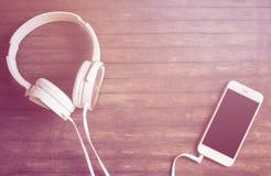 白色电话和耳机平的位置在木桌上 温暖的桃红色光定了调子照片 免版税库存图片