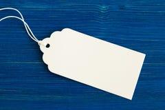 白色白纸价牌或标号组在蓝色木背景 免版税库存图片