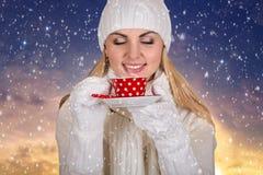 白色的一个少妇编织了他喝从一个美丽的杯子的热的咖啡的衣裳 图库摄影