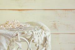 白色的图象成珠状在葡萄酒桌上的项链和金刚石冠状头饰 被过滤的葡萄酒 选择聚焦 库存图片
