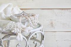 白色的图象成珠状在葡萄酒桌上的项链和金刚石冠状头饰 被过滤的葡萄酒 选择聚焦 图库摄影