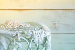 白色的图象成珠状在葡萄酒桌上的项链和金刚石冠状头饰 被过滤的葡萄酒 选择聚焦 免版税库存图片